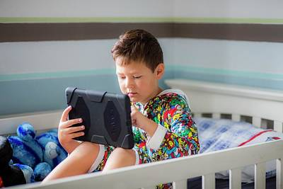 Boy Sitting In Bed Using A Digital Tablet Poster