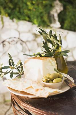 Cheese, Green Olives, Crackers And Olive Oil On Outdoor Table Poster
