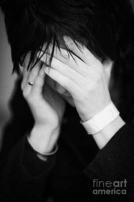 Close Up Of Young Dark Haired Teenage Man Sitting With His Head In His Hands Hiding His Face Staring Poster