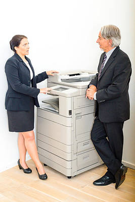 Colleagues Talking At  Copying Machine In The Office Poster