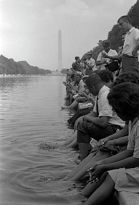 Demonstrators Sit Along The Reflecting Poster