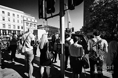early morning commuters waiting to cross the road pedestrian crossing London England UK Poster