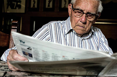 Elderly Man Reading A Newspaper Poster by Mauro Fermariello