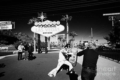 elvis impersonator taking photos with tourists at the welcome to fabulous Las Vegas sign Nevada USA Poster by Joe Fox