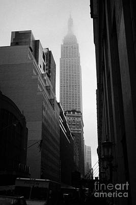 empire state building shrouded in mist in amongst dark cold buildings on 33rd Street new york city Poster