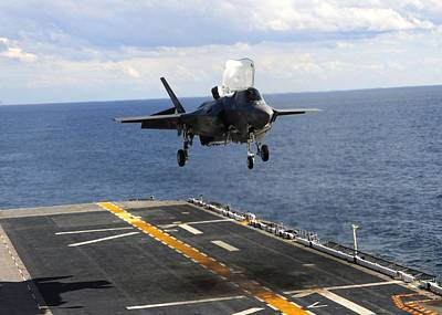 F 35 Joint Strike Fighter Landing Vertically On Us Marine Assault Carrier Poster by US Military - L Brown
