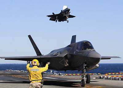 F 35s Landing On The Flight Deck Of Assault Carrier Poster by US Military - L Brown