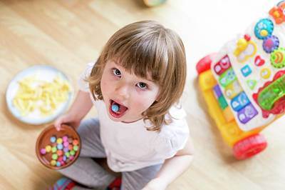 Girl Sitting On Floor With Bowl Of Sweets Poster