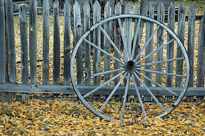 Golden Leaves And Old Wagon Wheel Against A Fence Poster