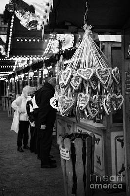 heart shaped Lebkuchen hanging on a christmas market stall with tourists browsing in Berlin Germany Poster by Joe Fox
