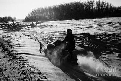 man on snowmobile crossing frozen fields in rural Forget canada Poster