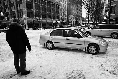 man watching car travelling along snow covered city streets in Saskatoon Saskatchewan Canada Poster