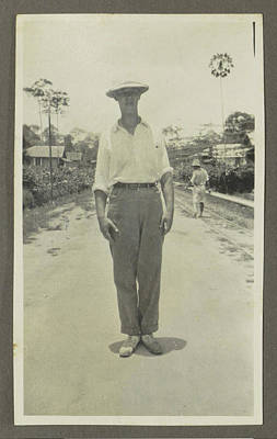 Man Wearing A Pith Helmet Posing On A Road Poster