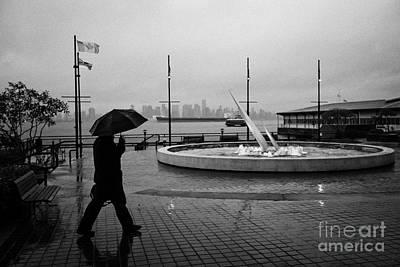 man with umbrella walking towards seabus terminal in the rain north Vancouver BC Canada Poster by Joe Fox