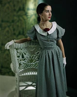 Model In A Striped Dress Resting On A Wicker Poster