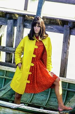 Model On A Boat In A Yellow Over Coat And A Red Poster