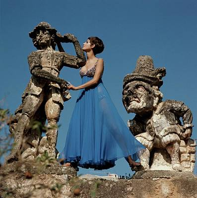 Model Standing Between Statues At The Villa Poster