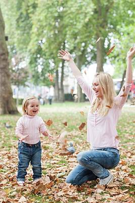 Mother And Daughter Playing With Leaves Poster