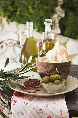 Olives, Salami, Crackers And Olive Oil On Table Out Of Doors Poster
