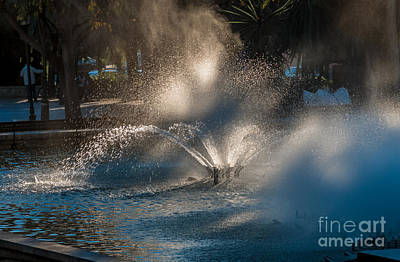 Ornamental Fountain In A Pond With Blurred Light Reflections Poster