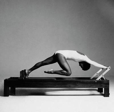 Paula Kelly Exercising On The 'reformer' Machine Poster by Francesco Scavullo