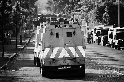 Psni Land Rovers Head Up The Crumlin Road Towards Loyalists At Ardoyne Shops Belfast 12th July Poster by Joe Fox