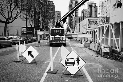 road closed to traffic to allow large articulated crane operate at building site Vancouver BC Canada Poster by Joe Fox