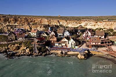 Seaside Village Under The Cliffs Poster by Tim Holt