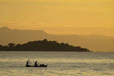 Silhouette Of Fishermen In Dugout Canoe Poster by Ian Cumming