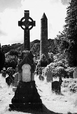 St Kevins Round Tower And Celtic Cross Headstone In Graveyard At Glendalough Monastic Site County Wicklow Ireland Poster by Joe Fox