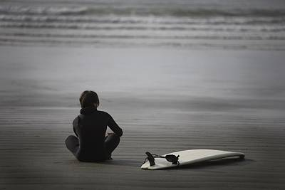 Surfer Sitting On Beach, Cox Bay Near Poster by Deddeda
