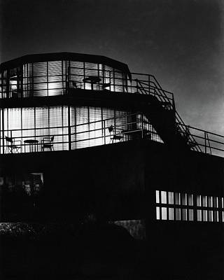 The Exterior Of A Spiral House Design At Night Poster