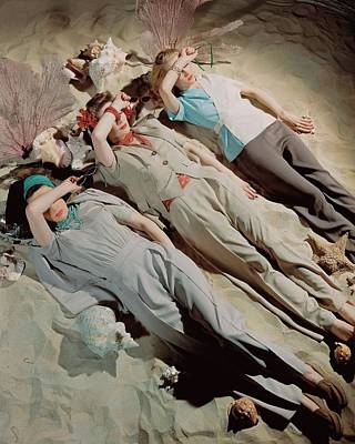 Three Models Lying Down On Sand Poster by John Rawlings