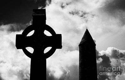top of St Kevins Round Tower and celtic cross headstone at Glendalough monastic site county wicklow ireland Poster by Joe Fox