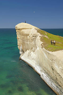 Tourists On Cliff Top At Tunnel Beach Poster by David Wall
