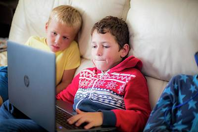 Two Boys Using A Laptop Sitting On Sofa Poster