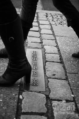 two women walking across double row of bricks across berlin to mark the position of the berlin wall berliner mauer Berlin Germany Poster by Joe Fox