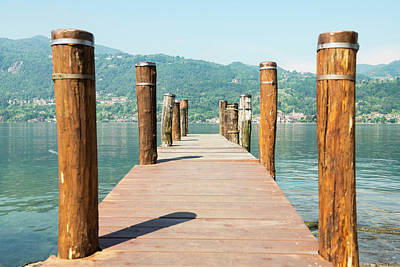 Wooden Dock And Posts On Lake Orta Poster by Mats Silvan