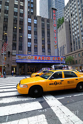 Yellow Cabs Pass In Front Of Radio City Music Hall Poster
