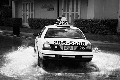 Yellow Taxi Cab Driving Through Streets Flooded By Heavy Rainfall Key West Florida Usa Poster by Joe Fox