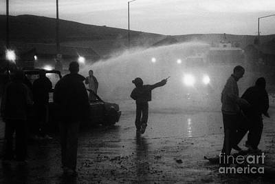 Youths Rioting Throwing Stones With Burned Out Car Being Hit By Water Canon On Crumlin Road At Ardoy Poster by Joe Fox