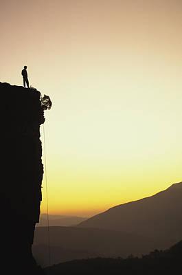 A Climber Stands Atop A Cliff Poster by Bill Hatcher