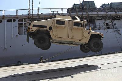 A Crane Lifts An M998 Humvee Poster by Stocktrek Images