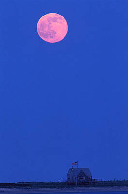 A Full Moon Rises Above The Shoreline Poster by Michael Melford