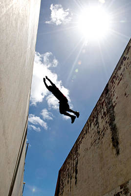 A Parkour Practitioner Jumps A Building Poster by Brooke Whatnall