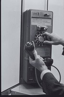 A Person Dialing A Pay Phone Poster