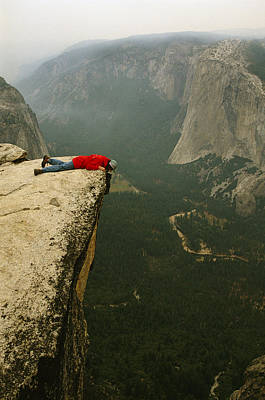 A Prone Man Peers Over Taft Point Poster by Bill Hatcher