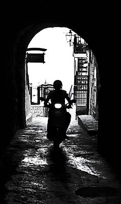 a scooter rider in the back light in a narrow street in Italy Poster