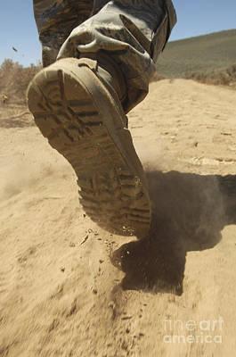 A U.s. Soldier Walks Along A Dirt Path Poster