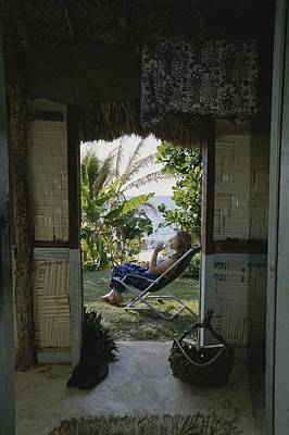 A Woman Relaxes Outside A Bure Hut Poster by Rich Reid